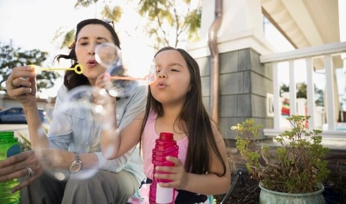 grandmother and granddaughter blowing bubbles gettyimages 680x402 1