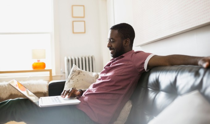 man sitting on couch with laptop gettyimages 680x402 1